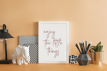 The design pastel orange desk with mock up photo frame, plant, elephant figure , notebooks and lamp. Modern creative space.