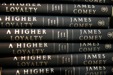 Copies of former FBI director James Comey's book are stacked for attendees to collect as they arrive to hear him speak at an onstage interview at George Washington University in Washington