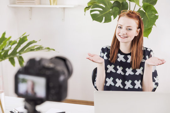 Young, redhead female blogger recording video at home studio for her channel using camera with a tripod.