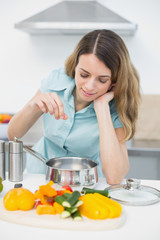 Content brunette woman cooking with vegetables standing in kitchen