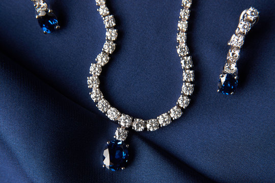Close-up of women's platinum necklace and earrings with a diamond and blue precious sapphire stone . Luxury female jewelry