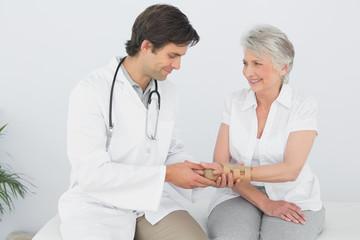 Male physiotherapist examining a senior womans wrist