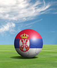 Soccer ball with Serbia flags in a green field