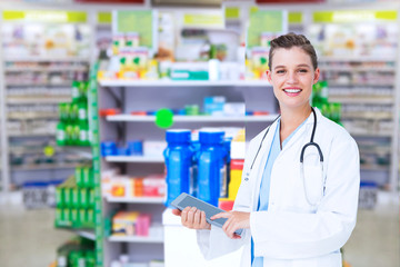 Happy doctor holding tablet pc against close up of shelves of drugs