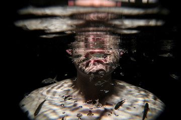 """Garra rufa obtusas, also known as """"doctor fish"""", swim around the face of a man as he relaxes in a hot spa pool in Kangal"""
