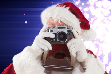 Santa is taking a picture against light design shimmering on purple