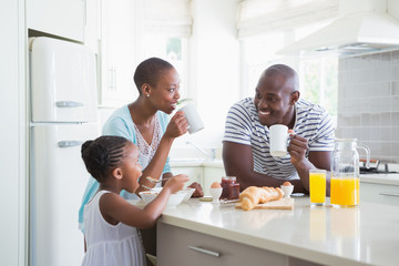 Happy family sitting and taking breakfast