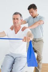 Therapist massaging mans shoulder in gym hospital