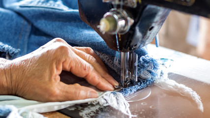 Repair jeans with an old sewing machine.