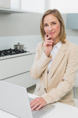 Portrait of a businesswoman using laptop in kitchen