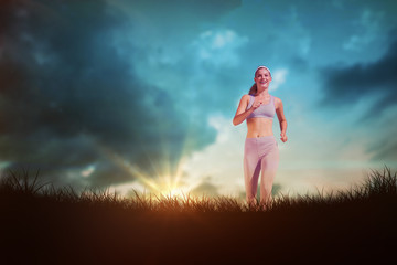 Sporty blonde jogging towards camera against blue sky over grass