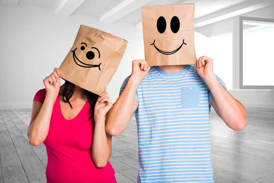 Young couple with bags over heads against white room with windows