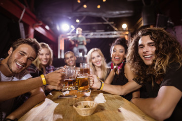 Portrait of happy friends toasting beer glasses while sitting at table