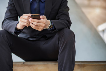 Young Asian Businessman using mobile phone in the city outside, handsome Man in suit sitting and hand touching screen on cellphone. Smart business and Technology concepts