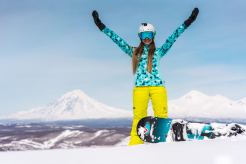 Happy young woman with snowboard in front of volcanos