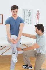 Male therapist assisting man with stretching exercises