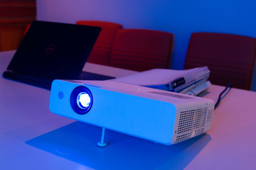 projector connected to Laptop for presentation in a meeting room with files folder and files document on table, business concept.