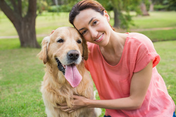 Pretty brunette looking at camera with her dog