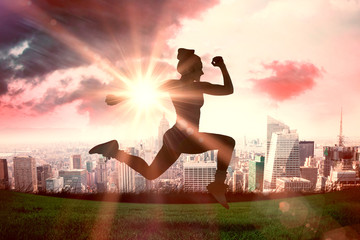 Fit brunette running and jumping against sun shining over city