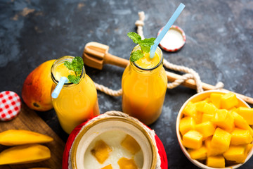 Mango Lassi or smoothie in big glass or small bottles with curd, cut fruit pieces and blender. Moody background, selective focus