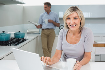 Woman using laptop and man reading newspaper in kitchen