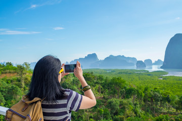 Young traveler woman backpacker use mobile phone take a photo of beautiful of sunrise nature at top of mountain view,Freedom wanderlust concept,Khao Samed Nang Chee,Phang Nga,Thailand