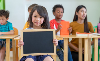Kid girl holding blank blackboard with diversity friends and teacher at background,Kindergarten preschool,mock up for adding text.back to school concept,children group student.