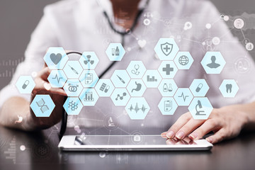 Medical doctor working with modern computer virtual screen interface. EMR, EHR, Electronic Health Records.