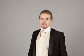 Portrait of handsome young man in a tuxedo. Fashionable clothing for the festive evening on gray background with copyspace