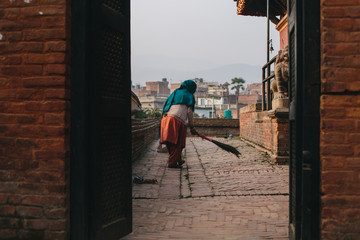 Woman clean small Temple area in old city Bhaktapur, Nepal