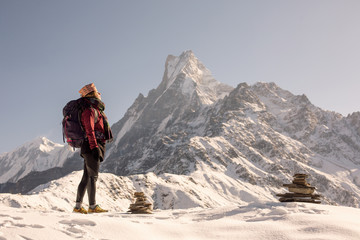 Female Traveller relaxing on top of snow high mountain and enjoying view of Fishtale mountain, freedom travel concept, nepali style hat