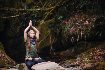 Young woman tourist sitting in misty tropical jungle forest in lotus position, relaxing and meditate