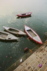 Old boats and woman swimming in Ganga river, Varanasi, India