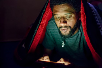 Young african man using mobile phone in dark bedroom lying on bed