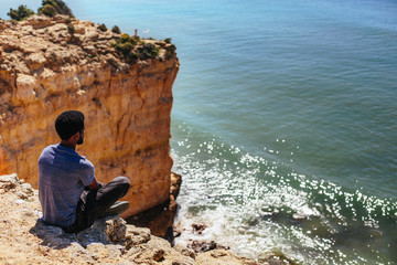 Mixed race african Man seating on beautiful cliff, looking to ocean, enjoy travel holiday. Algarve, Portugal