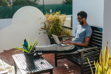 Young black man wearing glasses using laptop at home. Freelance worker, freedom and enjoy summer day