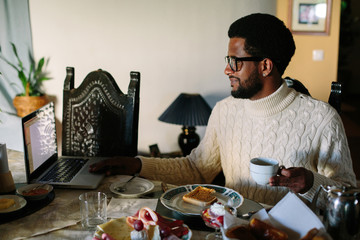 Portrait of young African man wearing glasses using laptop and have breakfast at home