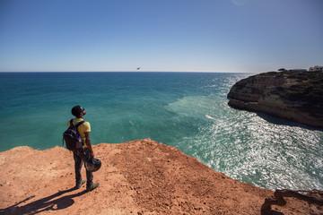 Man with dark skin, wearing sunglasses standing on beautiful cliff, looking to ocean, enjoy motor travel holiday . Algarve, Portugal