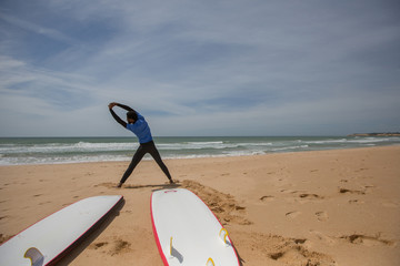 Surf longboards and surfer man doing exercises before surfing on ocean beach. Mixed rice male with dark skin, african hairstyle