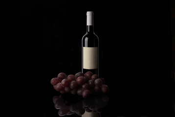 Red wine bottle and grape on black background