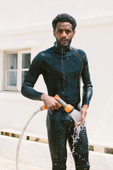 Mixed race surfer man taking shower outdoor after surfing lessons