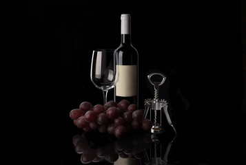 Red wine bottle, empty wine glass, corkscrew and grape on black background