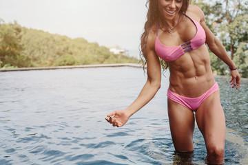 Beautiful female athlete wearing pink bikini in swimming pool outdoor