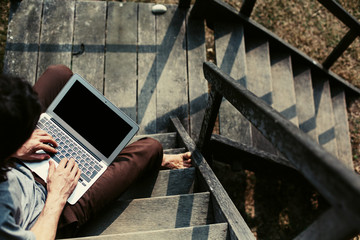 Freelancer man working with laptop computer sitting outdoor near village resort house on wooden stairs steps