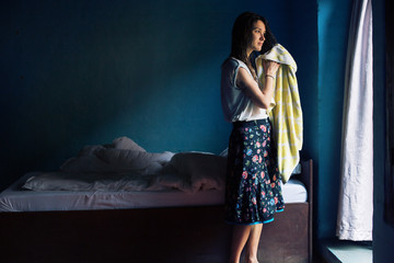 Young woman drying hair with towel in atmospheric village room with balcony and blue color wall