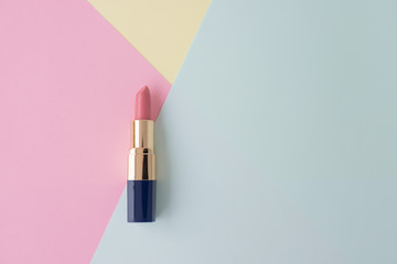 Flat lay of creative female cosmetic for pink lipstick on the colorful background with copy space