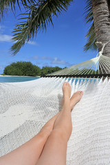 POV of a woman lay on a hammock relaxing in Muri lagoon in Rarotonga Cook Islands
