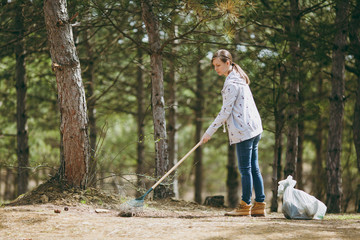 Young woman in casual clothes cleaning and using rake for garbage collection near trash bags in park or forest. Problem of environmental pollution. Stop nature garbage, environment protection concept.