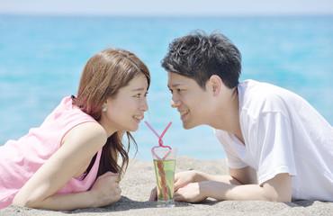 ビーチでトロピカルドリンクを飲む若いカップル