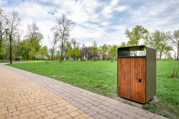 A wooden and metallic trash bin in the Natalka park of Kiev, Ukraine, close to the Dnieper river in spring